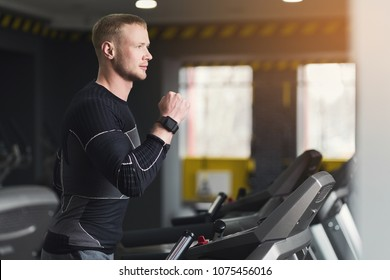 Young handsome man with fitness tracker in sport club. Cardio workout, running on treadmill. Healthy lifestyle, guy training in gym, side view, copy space