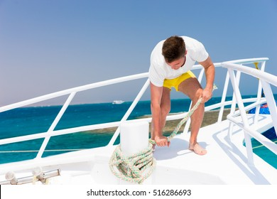 Young handsome man fixes rope on yacht at a sunny summer day, beautiful sea on background