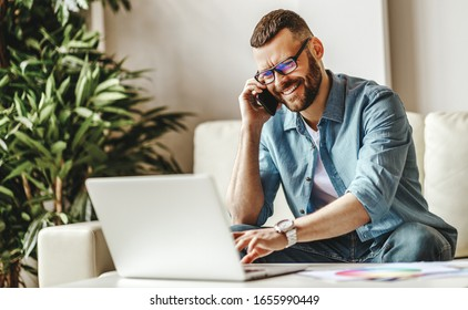 young handsome man freelancer working at home on a computer