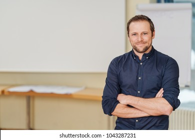 Young handsome man frontal portrait standing indoors with arms crossed, wearing black shirt with rolled up sleeves, copy space