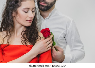 A young, handsome man gently covers his beautiful wife. During this time, one red rose. The girl is dressed in a red dress, a guy in a white shirt. On a white background.