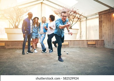 Young handsome man in glasses throwing steel petanque ball, his friends smiling standng behind him