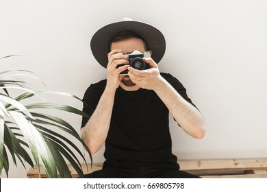 Young handsome man in grey hat and black outfit sits on wooden pallet bench and takes pictures with old film camera in white sunlit big loft room