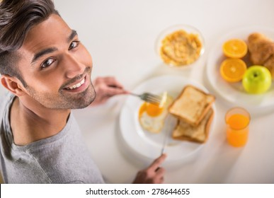Young handsome man in grey t-shirt eating breakfast.