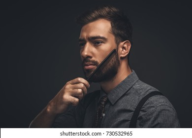 Young handsome man grooming his beard with a comb