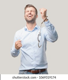 young handsome man with handcuffs celebrating his triumph wearing a blue t shirt . person isolated against monochrome background