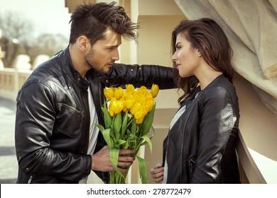 Young handsome man handing flowers