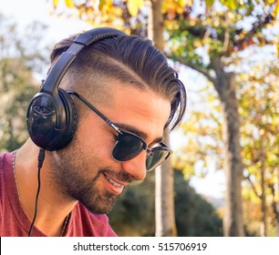 Young handsome man happy with headphones listening to music in a park outdoor - Close up portrait of a beautiful man smiling