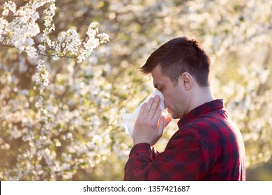 Young handsome man having allergy symptoms beside blooming tree in spring