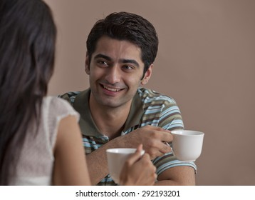 Young handsome man having hot drink with woman