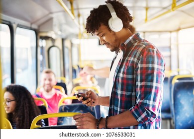 Young handsome man with a headset on is listening to music while looking at his phone and standing on the bus.