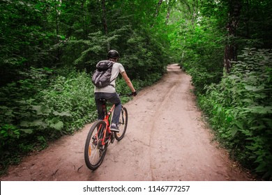 Young handsome man in helmet riding a bicycle on forest path among trees. Sports and healthy lifestyle. Trip to rainforest