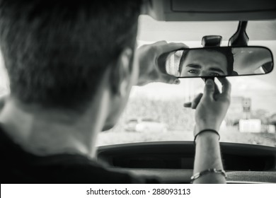 Young handsome man in his car adjusting rear view mirror during day