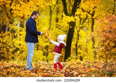 A young handsome man and his little lovely daughter in a bright red jacket walking in a park on a sunny autumn day