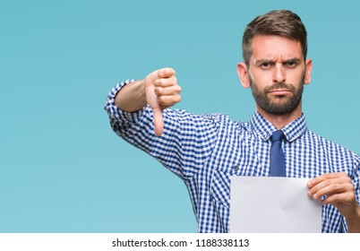 Young handsome man holding blank paper over isolated background with angry face, negative sign showing dislike with thumbs down, rejection concept