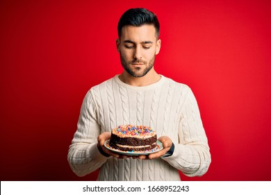 Young handsome man holding colorful birthday sweet cake over red isolated background with a confident expression on smart face thinking serious