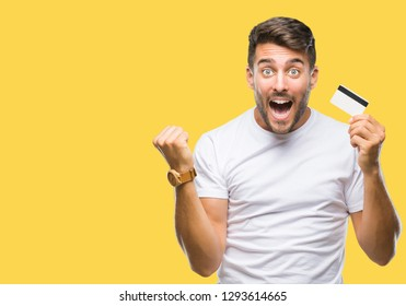 Young handsome man holding credit card over isolated background screaming proud and celebrating victory and success very excited, cheering emotion