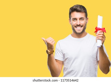 Young handsome man holding degree over isolated background pointing and showing with thumb up to the side with happy face smiling