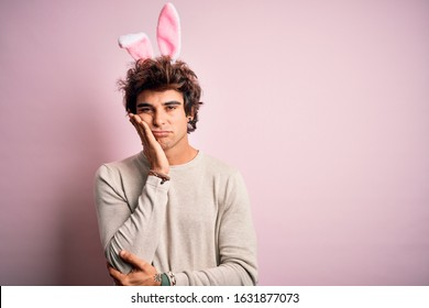 Young handsome man holding easter rabbit ears standing over isolated pink background thinking looking tired and bored with depression problems with crossed arms.