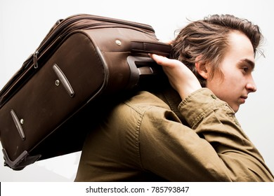 Young handsome man holding heavy brown suitcase on his back on the white background close up. Travel and tourism concept. Selective focus and shallow DOF