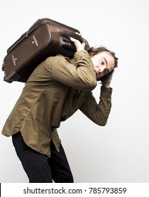 Young handsome man holding heavy brown suitcase on his back on the white background. Travel and tourism concept. Selective focus and shallow DOF