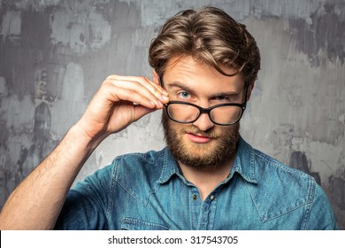 Young handsome man holding his glasses