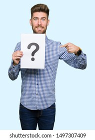 Young handsome man holding paper with question mark with surprise face pointing finger to himself