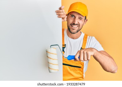 Young handsome man holding roller painter over white banner winking looking at the camera with sexy expression, cheerful and happy face.