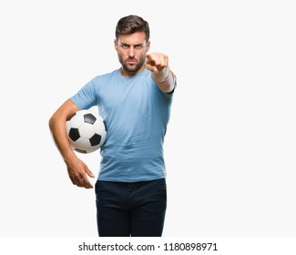 Young handsome man holding soccer football ball over isolated background pointing with finger to the camera and to you, hand sign, positive and confident gesture from the front