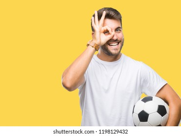 Young handsome man holding soccer football ball over isolated background with happy face smiling doing ok sign with hand on eye looking through fingers