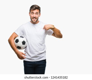 Young handsome man holding soccer football ball over isolated background with surprise face pointing finger to himself