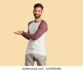 Young handsome man holding something with hands