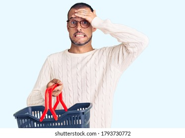 Young handsome man holding supermarket shopping basket stressed and frustrated with hand on head, surprised and angry face
