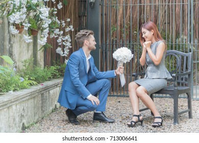 Young handsome man holds a white bouquet for his girlfriend to get married in the garden.