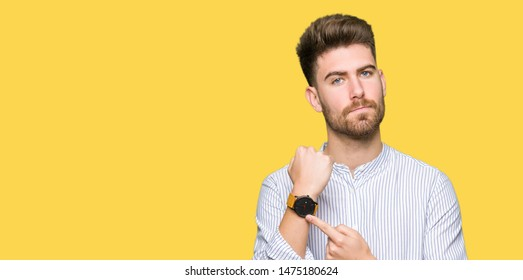 Young handsome man In hurry pointing to watch time, impatience, upset and angry for deadline delay