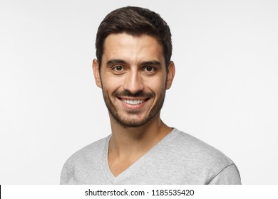 Young handsome man isolated on gray background, smiling happily and friendly at camera, looking confident and relaxed