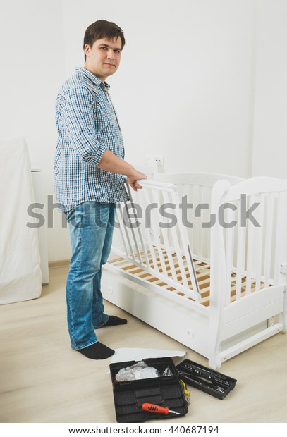 Young handsome man in jeans and shirt assembling baby's cot