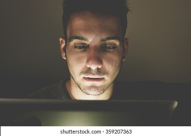 Young handsome man at laptop computer with light reflection from the screen to the face - technology, internet and people concept