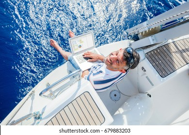 Young and handsome man with laptop computer on sailboat