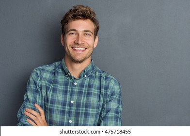 Young handsome man leaning against grey wall with arms crossed. Cheerful man laughing and looking at camera with a big grin. Portrait of a happy young man standing over grey background.