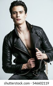 young handsome man, leather jacked on naked torso, emotional posing, white background, modern guy, lifestyle people concept