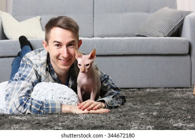 Young handsome man lies with cat on floor at home