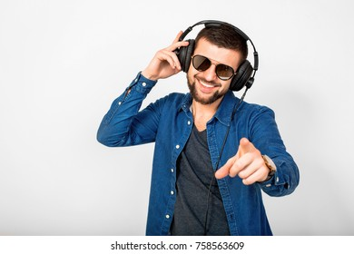 young handsome man listening to music in headphones, white studio background, isolated, smiling, happy, pointing finger