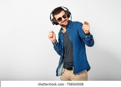 young handsome man listening to music in headphones, white studio background, isolated, smiling, happy