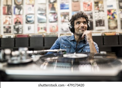 Young handsome man listening a record in the vinyl record store