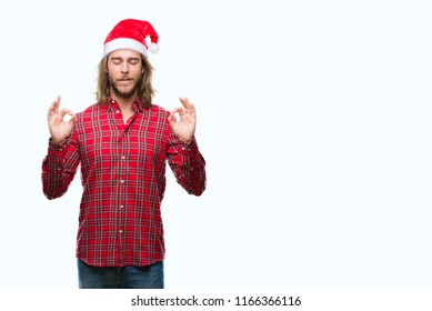 Young handsome man with long hair wearing santa claus hat over isolated background relax and smiling with eyes closed doing meditation gesture with fingers. Yoga concept.