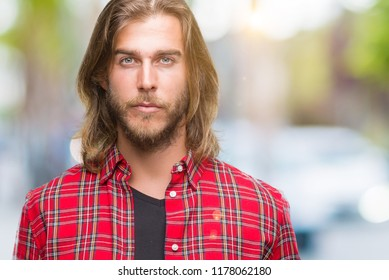 Young handsome man with long hair over isolated background with serious expression on face. Simple and natural looking at the camera.