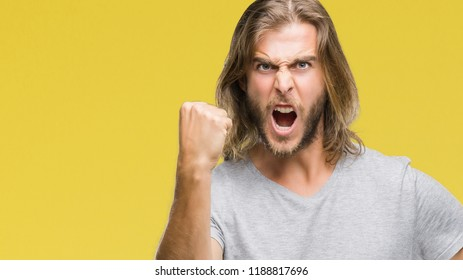 Young handsome man with long hair over isolated background holding football ball annoyed and frustrated shouting with anger, crazy and yelling with raised hand, anger concept