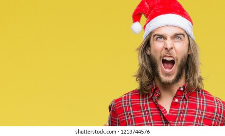 Young handsome man with long hair wearing santa claus hat over isolated background crazy and mad shouting and yelling with aggressive expression and arms raised. Frustration concept.