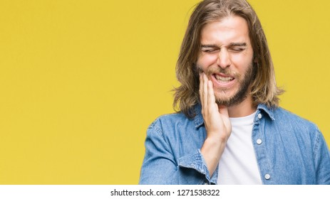 Young handsome man with long hair over isolated background touching mouth with hand with painful expression because of toothache or dental illness on teeth. Dentist concept.